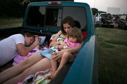 Danny Kinnard sleeps as his wife, Katy Kinnard, and daughter Gracie Kinnard, 3, from Waxahachie, waited for the sun to go down to watch a double feature at the Galaxy Drive-In in Ennis in 2009.