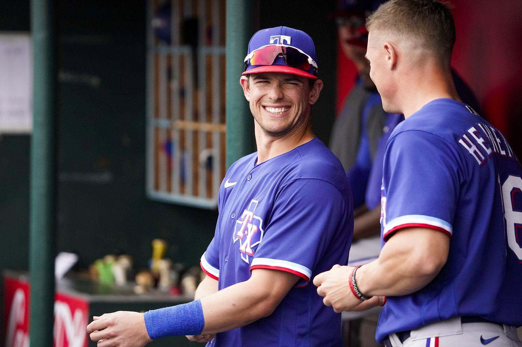 Texas Rangers infielder/outfielder Nick Solak laughs with outfielder Scott Heineman in the dugout during the fourth inning of a spring training game against the Los Angeles Angels at Tempe Diablo Stadium on Friday, Feb. 28, 2020, in Tempe, Ariz.