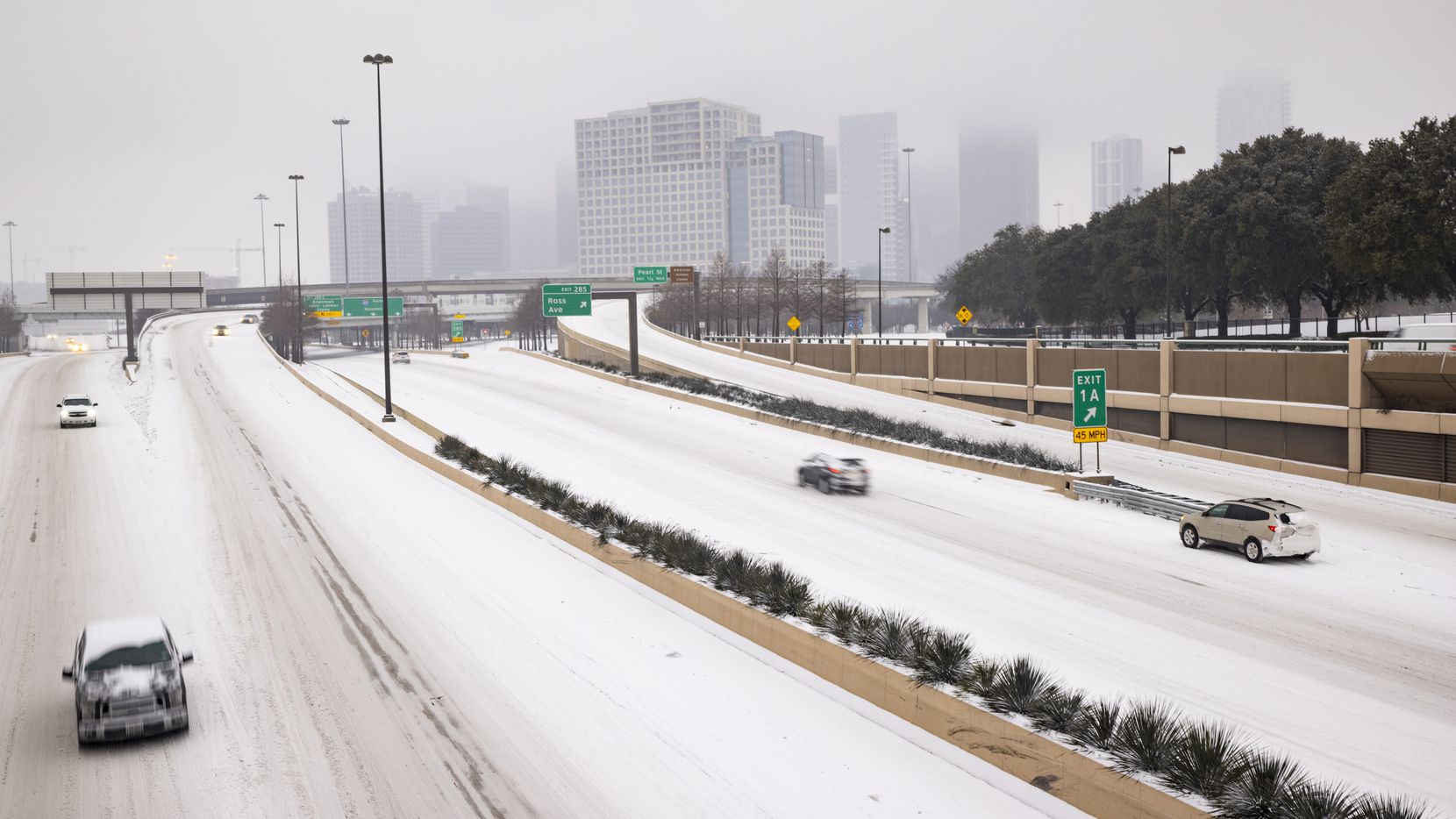 A foggy downtown and stalled car seen on a snowy and icy North Central Expressway in Dallas on Wednesday. Millions of Texans have lost power amid this record-breaking winter storm.
