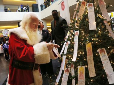 "In this file image, Santa selected an ""angel"" from the Salvation Army's Angel Tree at NorthPark Center after a kickoff parade on Black Friday."