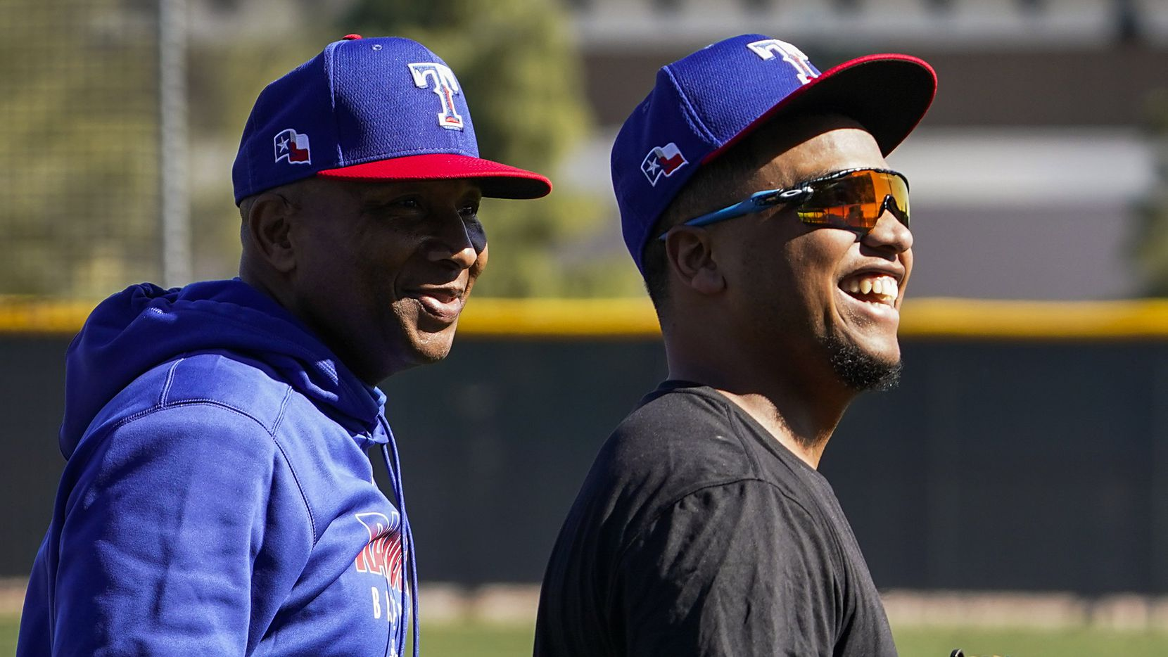 Texas Rangers outfielder Willie Calhoun (right) laughs with third base coach Tony Beasley during the first spring training workout for pitchers and catchers at the team's training facility on Wednesday, Feb. 12, 2020, in Surprise, Ariz.