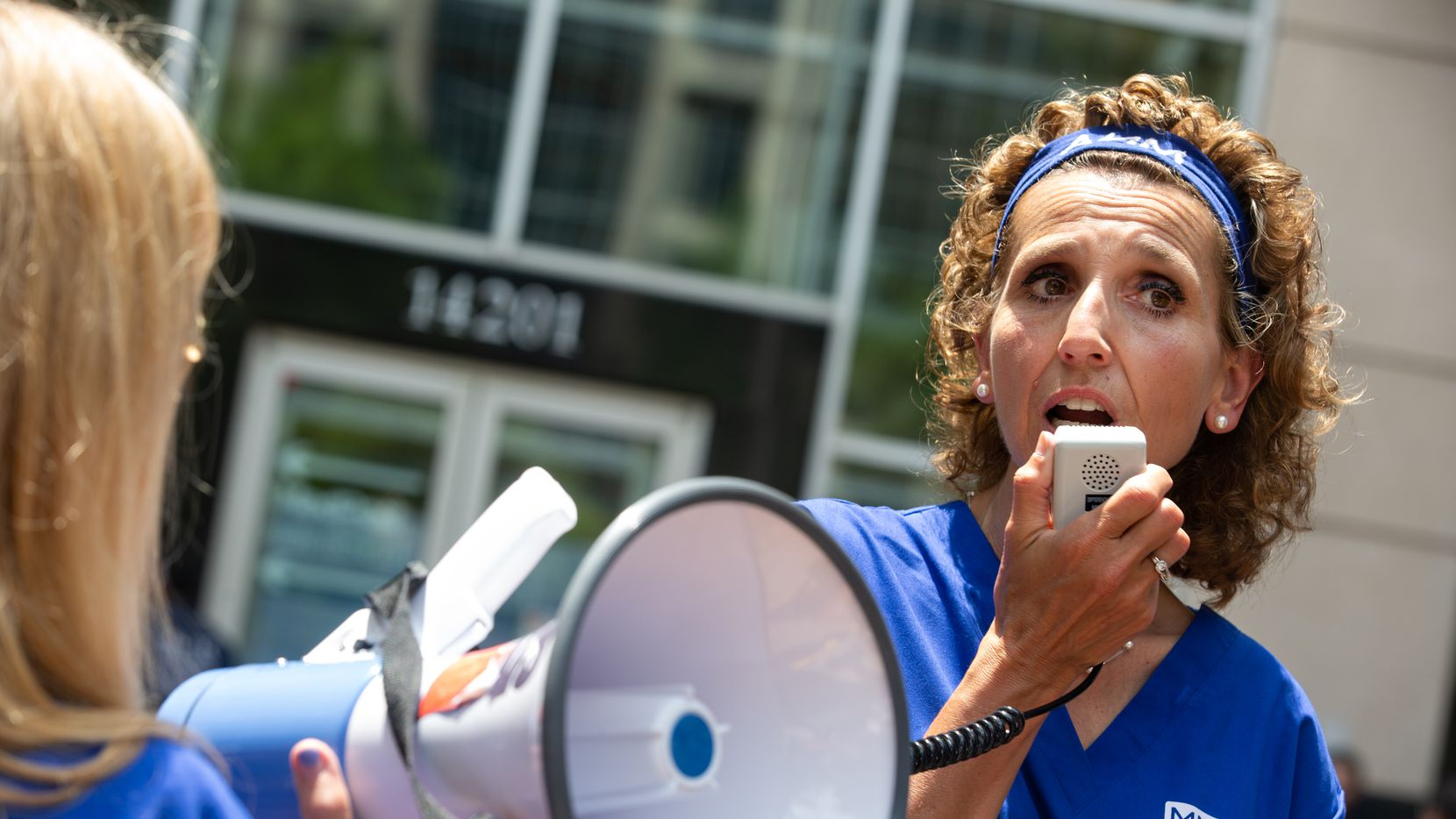 Marlena Pellegrino, a 44-year nurse at St. Vincent Hospital in Massachusetts, speaks to fellow protesters outside Tenet Healthcare's Farmers Branch headquarters after delivering a petition signed by 700 striking nurses on July 7, 2021.