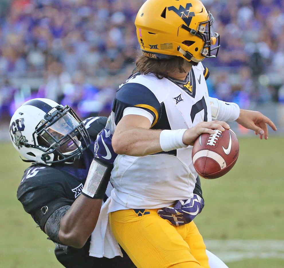 FILE - TCU defensive end Ben Banogu (15) pressures West Virginia quarterback Will Grier (7) in the fourth quarter during the West Virginia Mountaineers vs. the TCU Horned Frogs at Amon G. Carter Stadium in Fort Worth on Saturday, October 7, 2017. (Louis DeLuca/The Dallas Morning News)