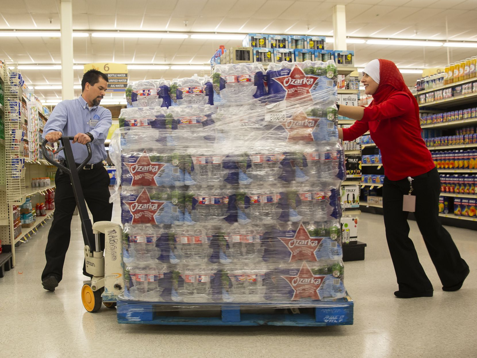 Maha Eldabaja, center store operations specialist, (right) helps Shaun Paeth, head of general merchandise, push a water pallet at Albertson's on March 20, 2020, in Colleyville. (Juan Figueroa/The Dallas Morning News)