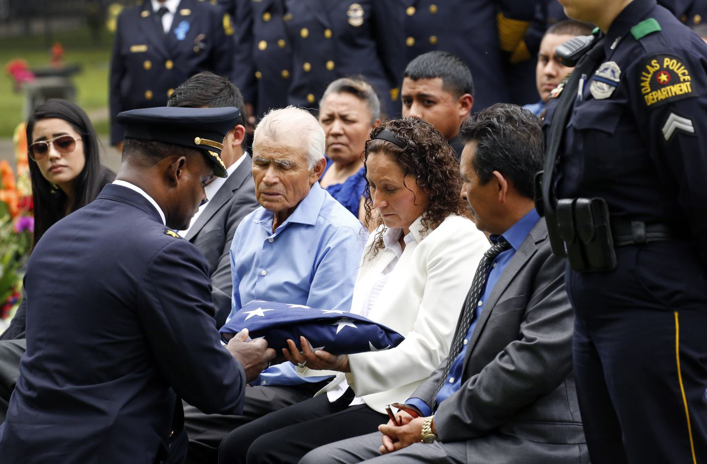 Dallas Police Deputy Chief Avery Moore kneels before and hands a folded U.S. flag to Juila Santander, mother of slain Dallas police officer Rogelio Santander, Jr., as he was laid to rest in the Garden of Honor at Restland Funeral Home and Cemetery in Dallas.