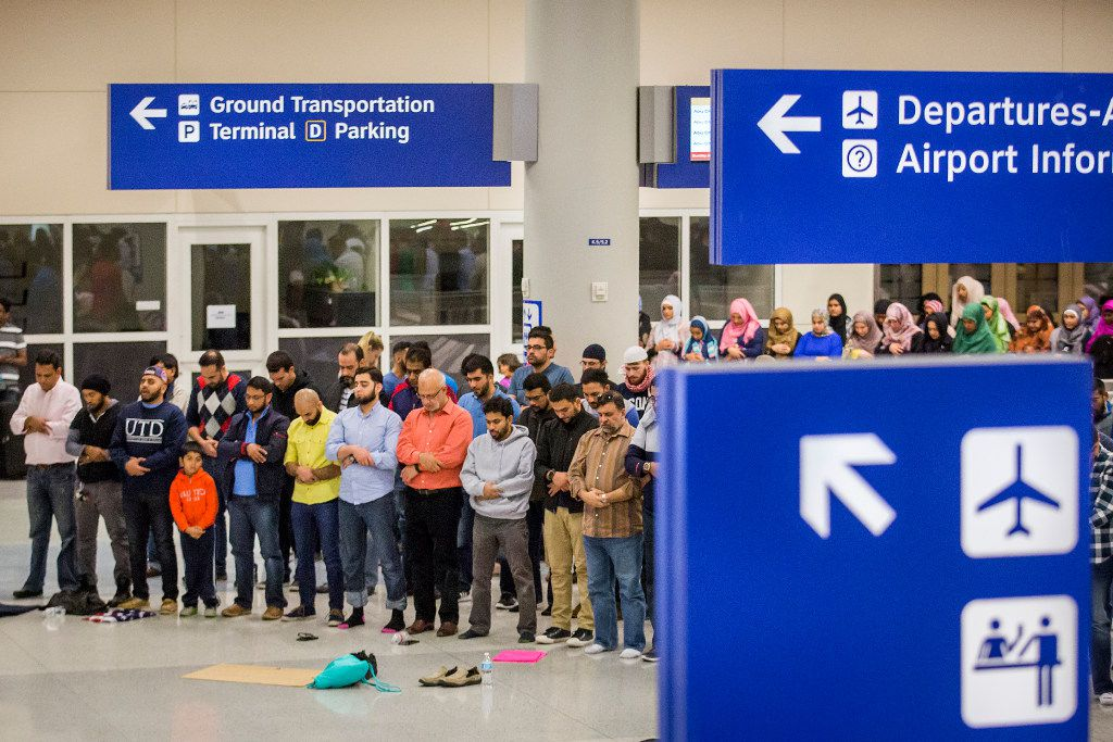 Muslim men set down their protest signs to take part in afternoon prayer at DFW International Airport where they gathered in opposition to President Donald Trump's executive order on Sunday, Jan. 29, 2017.