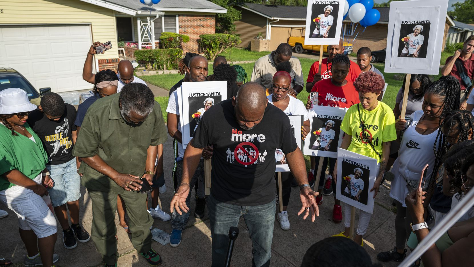 Ricardo Cooper (center) of Elijah Fellowship Community Church conducted a prayer vigil for Anita Thompson outside her home in east Oak Cliff on Sunday.