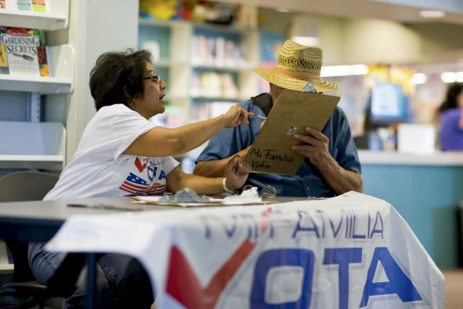 A volunteer with Mi Familia Vota, which helps Latinos become citizens and register to vote, helps a man with voter registration papers. Columnist Ruben Navarrette says Democrats have let Latinos down and will pay for it on Nov. 4.