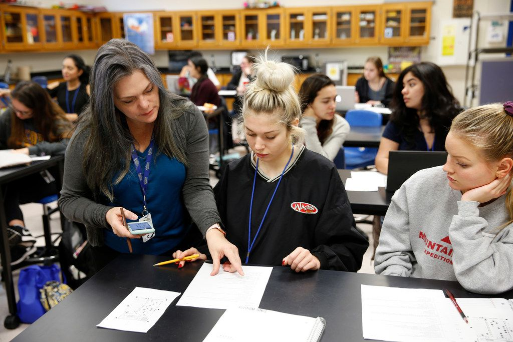 AP Environmental Science teacher Tina Littlejohn goes over a quiz question with Daniela Moneta, 17, and Grace Wadley, 17, at Frisco High School. Frisco ISD practices a small high school model. It is the state's fastest-growing school district.  (Vernon Bryant/The Dallas Morning News)