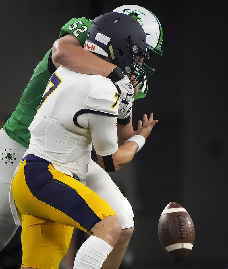 Highland Park quarterback  Brennan Storer (7) fumbles as he is hit by  Southlake Carroll defensive lineman Cade Parks (52) during the first half of a high school football game at AT&T Stadium on Thursday, Aug. 26, 2021, in Arlington.