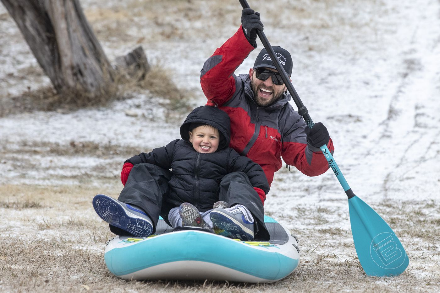 John Bain and his son, Everett, 3, sled down a hill on a paddleboard in the snow at Flag Pole Hill Park on Sunday, Feb. 14, 2021, in Dallas.