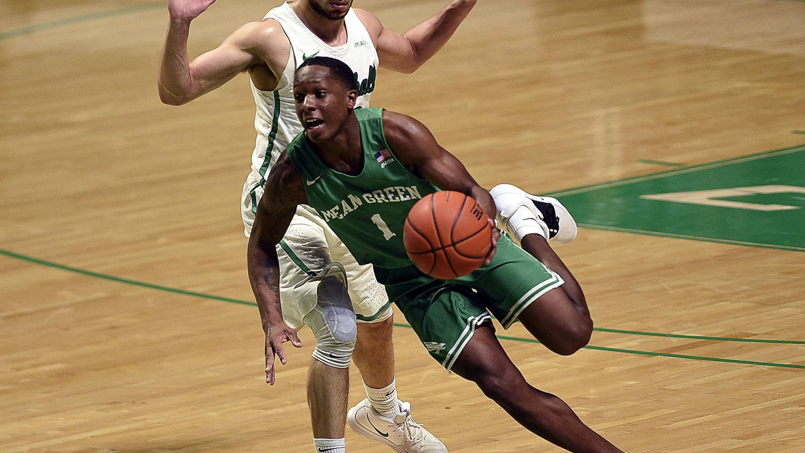North Texas guard Umoja Gibson (1) brings the ball up the court as Marshall guard Jarrod West defends during Marshall's 85-82 win over the Mean Green at the Super Pit in Denton.