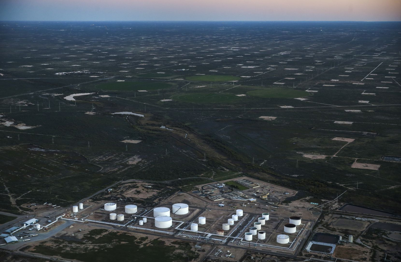 An oil tank farm sits in front of a production field speckled with pumpjack sites just west of Odessa.