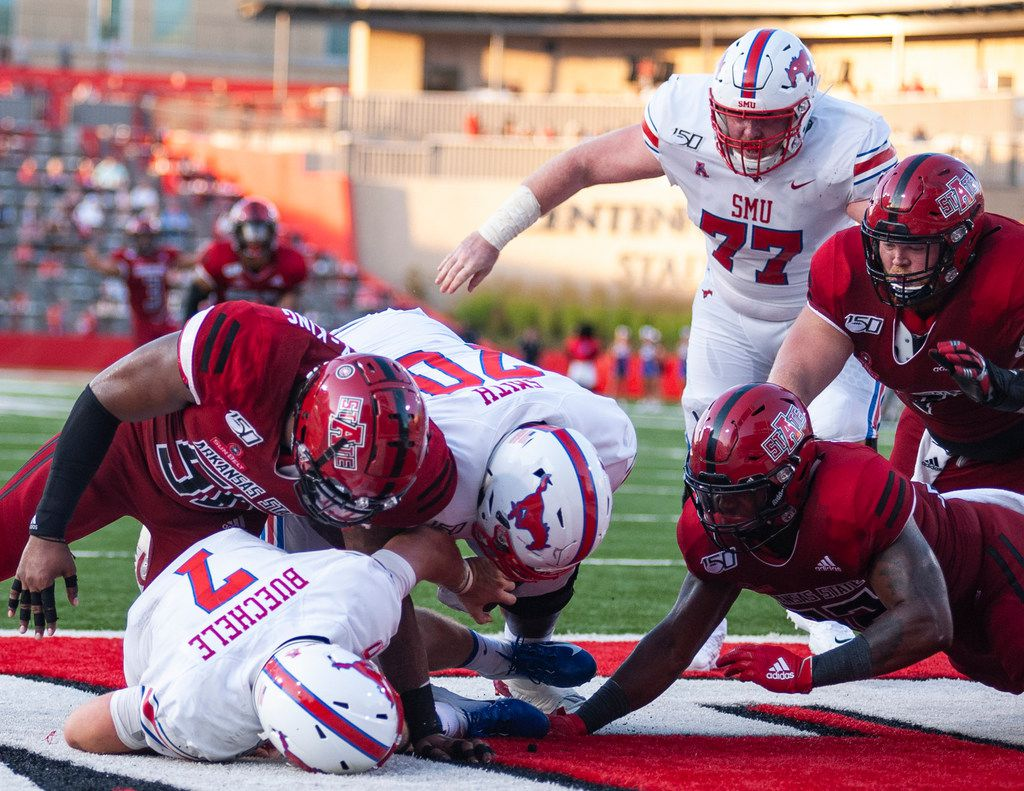 Arkansas State defensive end William Bradley King, upper left, sacks SMU quarterback Shane Buechele (7) in the endz one for a safety during the first half of an NCAA college football game Saturday, Aug. 31, 2019, in Jonesboro, Ark.