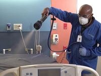 A health care worker sprays down a hospital bed with the continuously active disinfectant, SurfaceWise2.