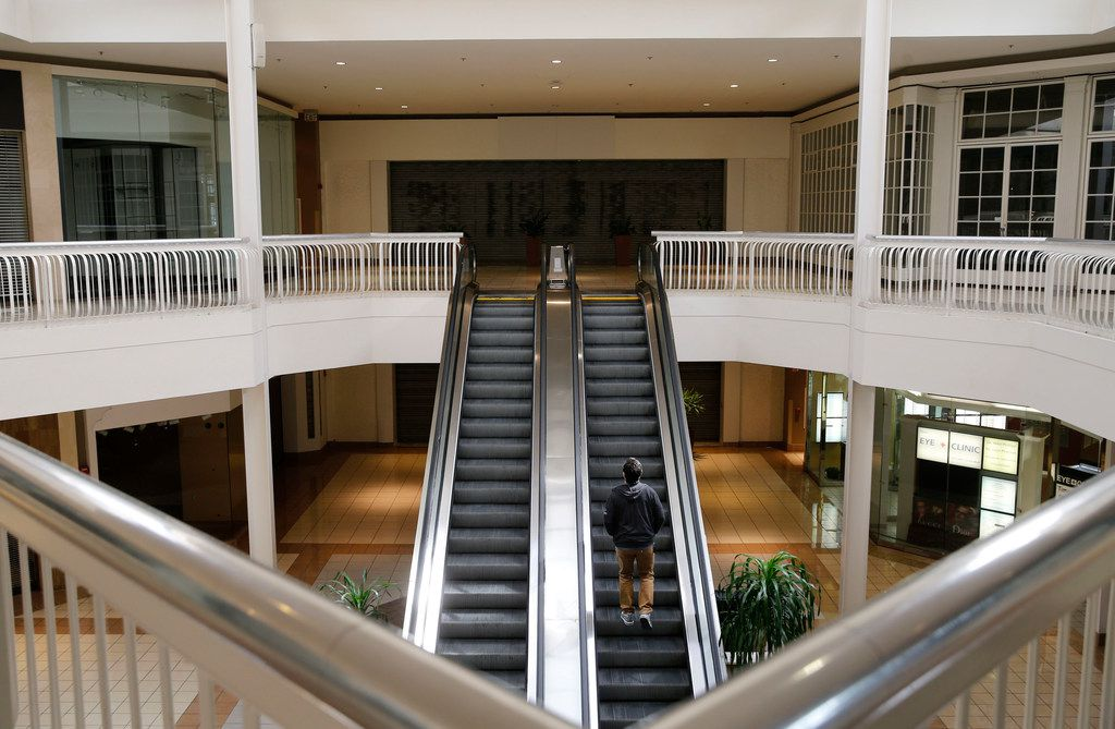 A man rides an escalator toward an empty storefront that used to be a Macy's at Collin Creek Mall in Plano.