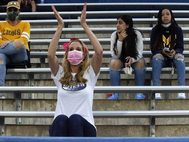 McKinney resident Cindy Philosfsky (center) dons a mask and practices social distancing as she cheers for her daughter who is a McKinney High School cheerleader during a game last year. The district has announced that it will continue requiring students and staff to wear masks.