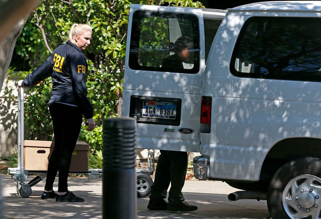 FBI agents loaded boxes into a van while federal agents raided Medoc Health Services in Dallas on May 9, 2018. Three defendants in the alleged scheme have accepted plea agreements.