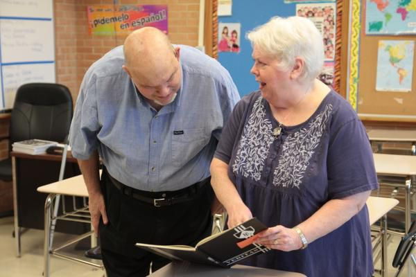 Bertucci flips through Bishop Lynch yearbook pages with her husband, Jim.