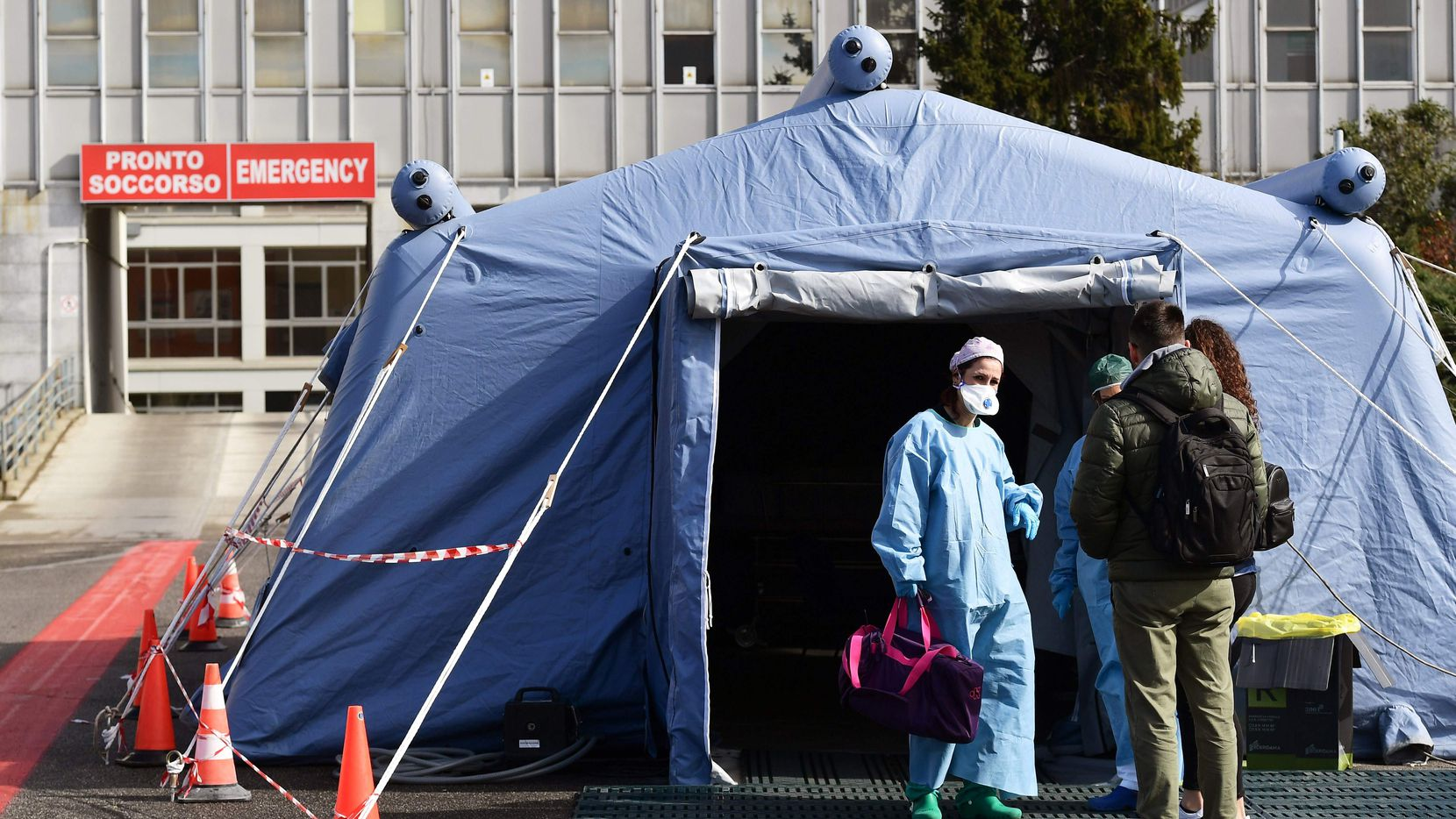People arrive at a pre-triage medical tent in front of a hospital in Cremona, Italy, on Wednesday.
