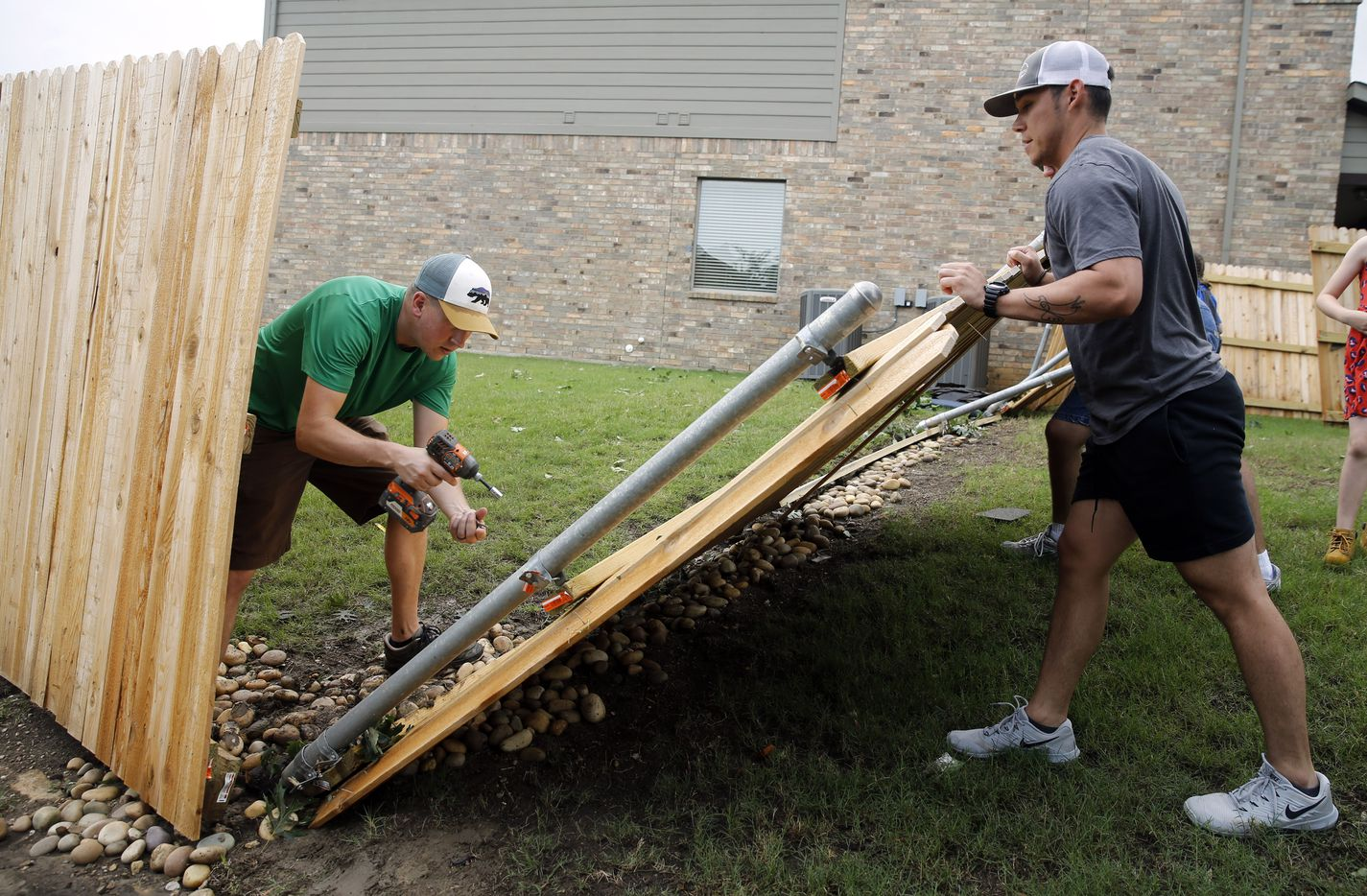 Neighbors, including Jon Lambrecht (left), help remove a downed fence on Oliver Drive in North Fort Worth after wind toppled trees and tore shingles off homes Wednesday.