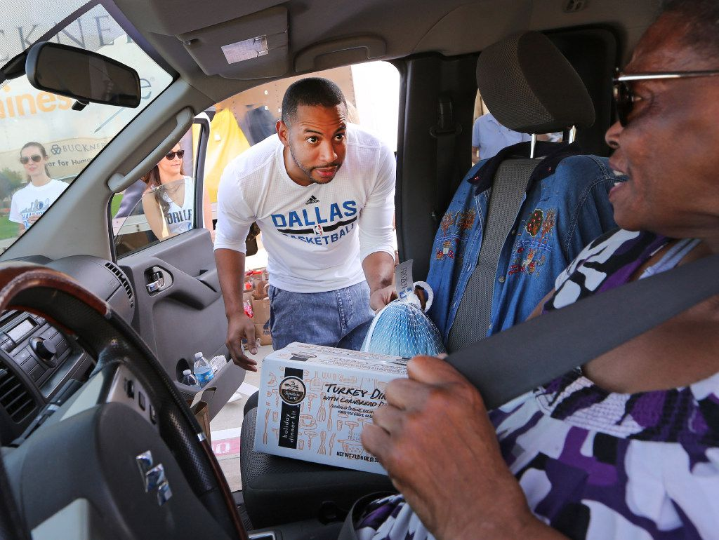 Thea Skinner, in car, watches as Dallas Mavericks player Devin Harris helps hand out supplies for Thanksgiving dinners, including 250 turkeys, to families in need at Buckner International in Mesquite on Thursday, November 17, 2016. (Louis DeLuca/The Dallas Morning News)