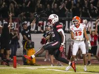 Rockwall-Heath running back  Zach Evans (26) scores on 17-yard touchdown run past Rockwall defensive back Cadien Robinson (13) during the first half of a District 10-6A high school football game at Wilkerson-Sanders Stadium on Friday, Sept. 24, 2021, in Rockwall.