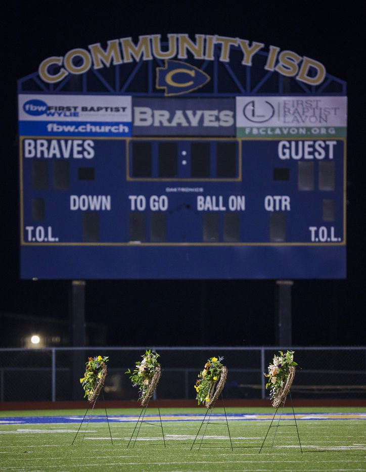 Four wreaths are lined up on the field at the Community ISD football stadium before a vigil for four students who were killed in a two-vehicle crash on Wednesday, Nov. 6, 2019, in Nevada, Texas.