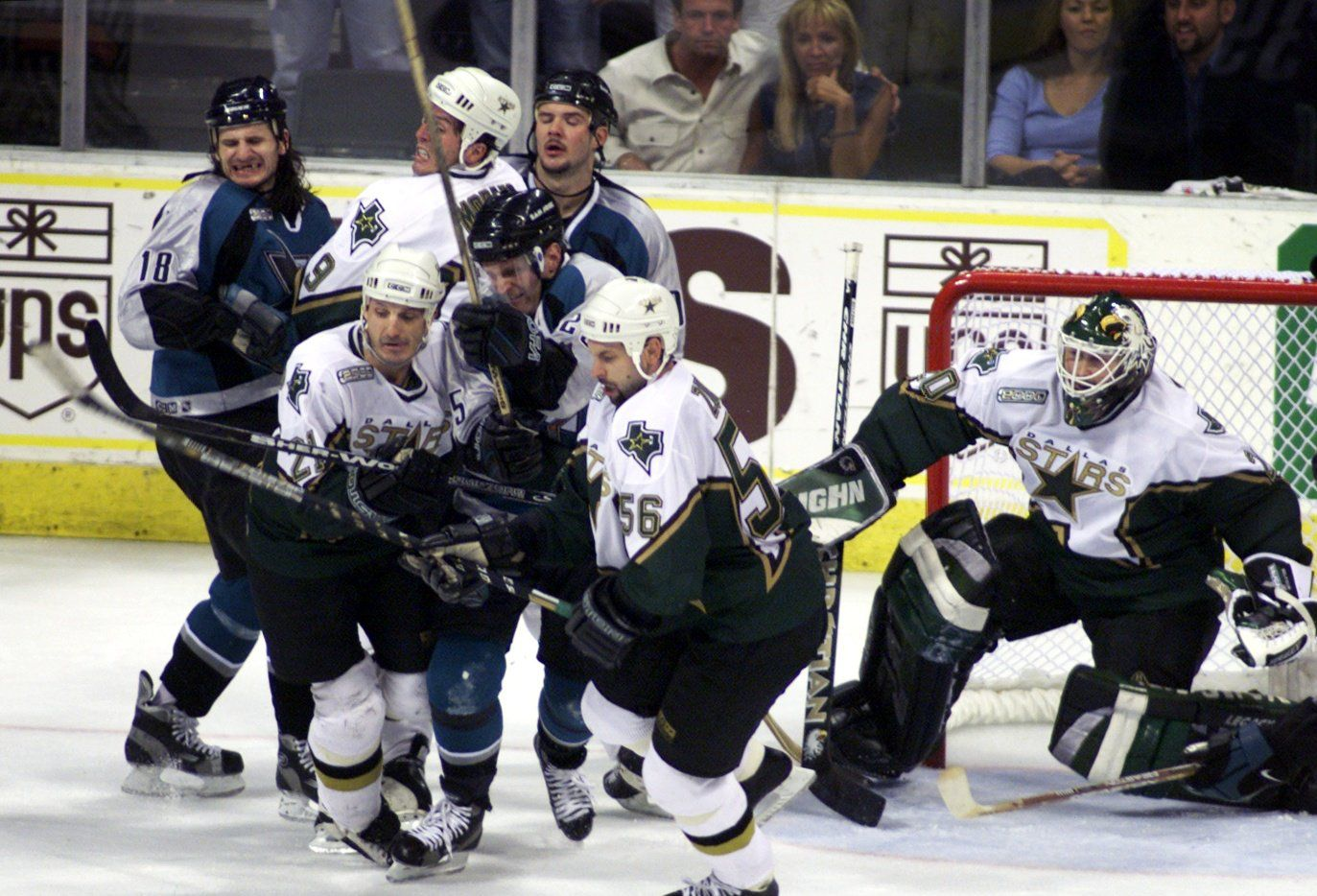 FILE - Dallas and San Jose players fight for the puck in front of Stars goalie Ed Belfour during the final minute of a playoff game at Reunion Arena in 2000. The players pictured are San Jose's Mike Ricci (18), Dallas' Mike Modano (9), Dallas' Guy Carbonneau (21), San Jose's Vincent Damphousse (25) and Dallas' Sergei Zubov (56).