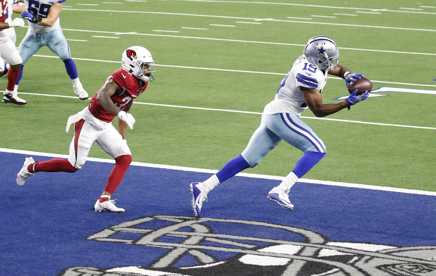 Dallas Cowboys wide receiver Amari Cooper (19) catches a pass for a touchdown in front of Arizona Cardinals cornerback Kevin Peterson (27) during the fourth quarter of play at AT&T Stadium on Monday, October 19, 2020 in Arlington, Texas. (Vernon Bryant/The Dallas Morning News)