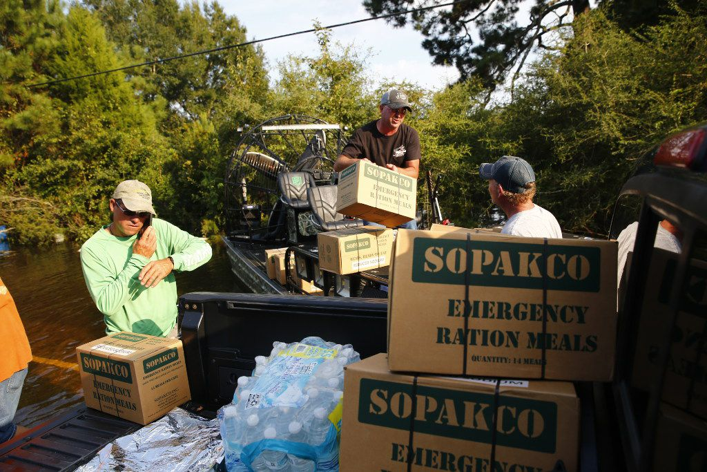Jody Anderson and Brooks Bonin unload Bonin's boat on the west end of FM 1131 to resupply Pine Forest after Hurricane Harvey on Sept. 3, 2017.