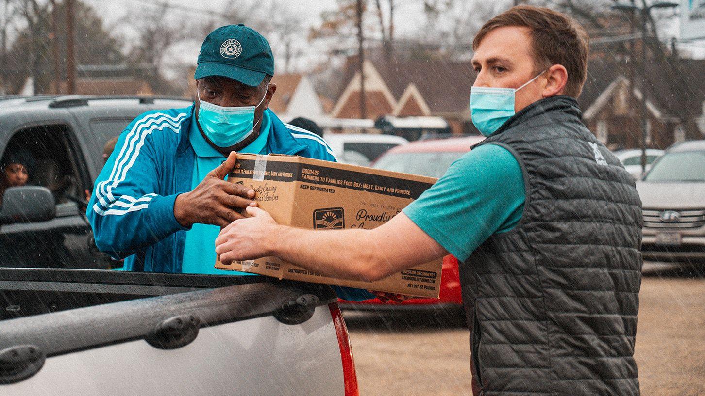 Socialwyze founder Cody Merrill and Texas Senator Royce West distribute food at Park South YMCA.