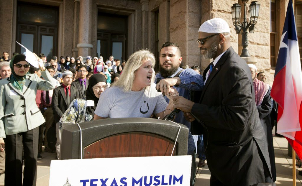 Protester Christine Weick wrestles away the microphone during the Texas Muslim Capitol Day in Austin, Texas, on Thursday, Jan. 29, 2015.