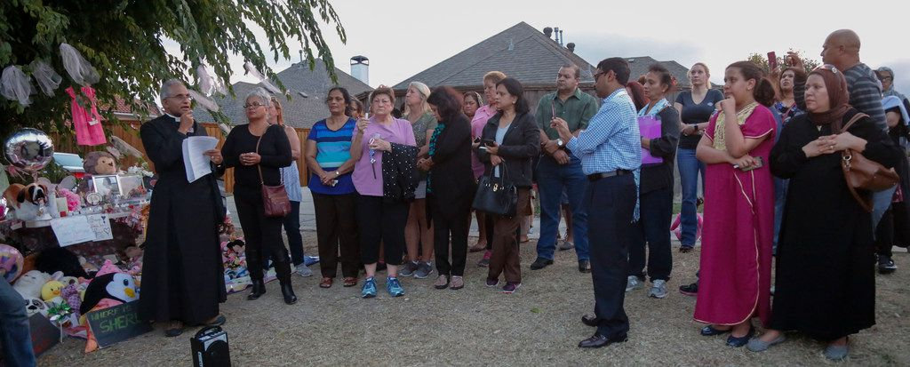 Father Thomas Ambalavelio, left, leads a prayer at a vigil for Sherin Mathews in Richardson, Texas Friday October 20, 2017. The vigil was held in an alley by a tree near her parents house where her father said he left the three-year-old girl on October 7, 2017.