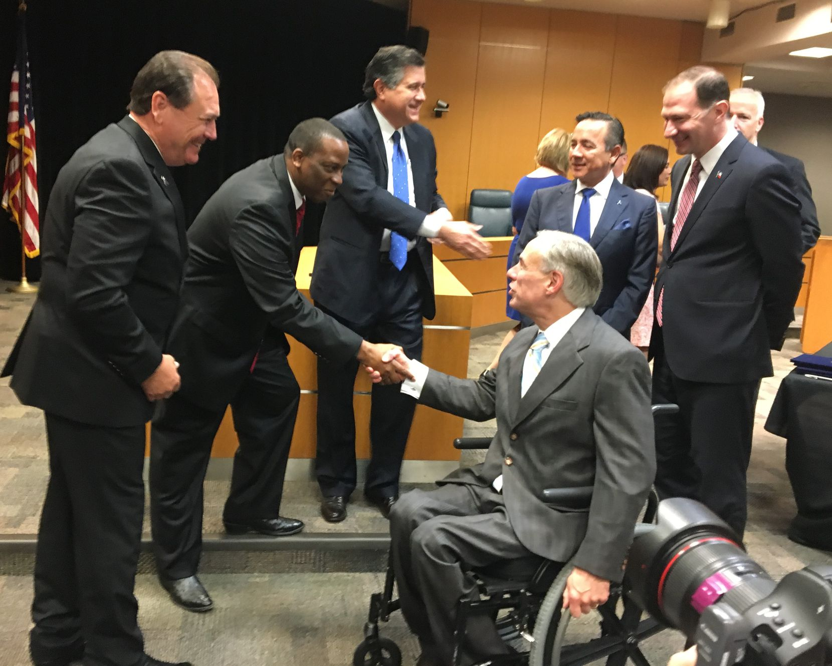 Gov. Greg Abbott shakes hands with executive commissioner of health and human services Charles Smith as protective services chief Hank Whitman, left, looks on. In background are four of nine lawmakers who joined the governor at a CPS bill signing -- from left, Rep. Richard Raymond, Sen. Carlos Uresti, Sen. Charles Schwertner and (partially obscured) Rep. James Frank.