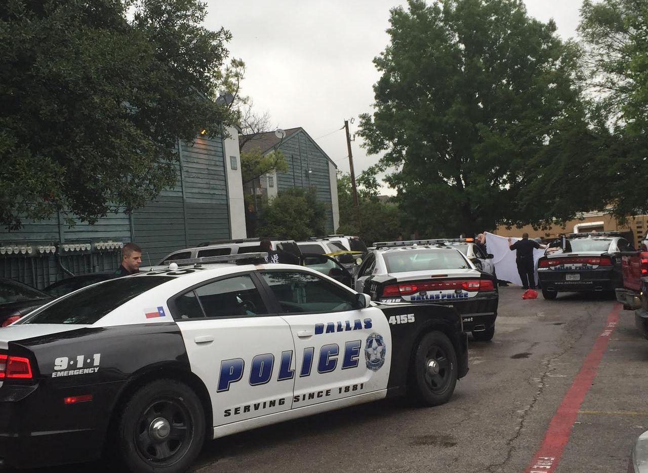 Policías de Dallas cubren un cuerpo sin vida mientras lo sacan de un auto en los departamentos Winding Way, en el Norte de Dallas, en abril del 2015. (DMN/NAHEED RAJWANI)