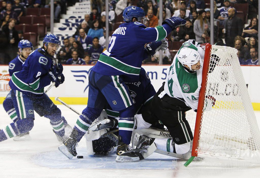 VANCOUVER, BC - NOVEMBER 17: Dan Hamhuis #2 of the Vancouver Canucks checks Jamie Benn #14 of the Dallas Stars into Canucks goaltender Roberto Luongo's net during the first period of their NHL game at Rogers Arena on November 17, 2013 in Vancouver, British Columbia, Canada. (Photo by Ben Nelms/Getty Images) 11182013xSPORTS