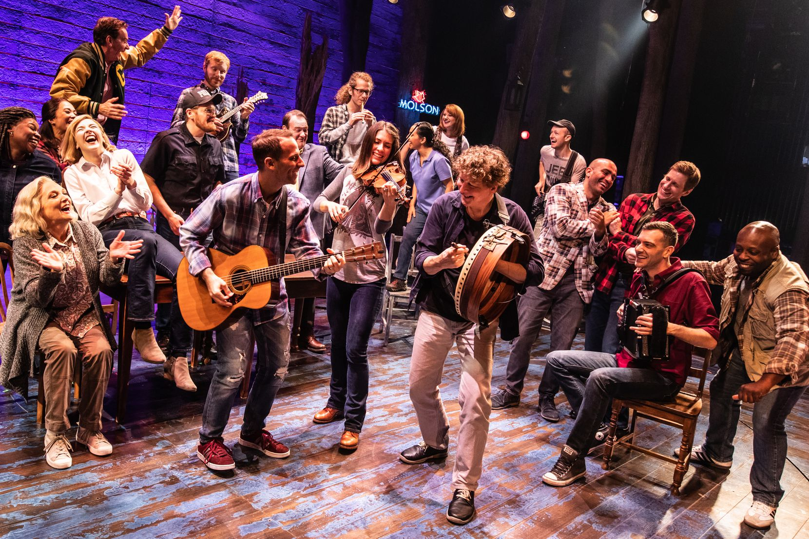 "The North American touring cast of ""Come From Away"" in an exuberant moment, including Dallas-area actors Julie Johnson, seated far left, and Chamblee Ferguson, standing far left (in letter jacket)."