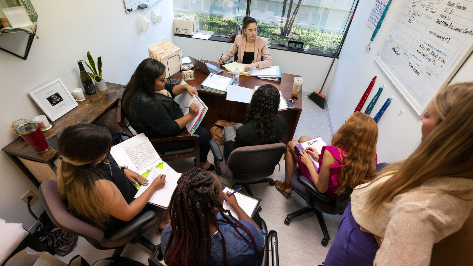 Madison Kitchen, behind desk, leads a meeting in her office at the Lumos Marketing Group in Far North Dallas. Through July, the Dallas-Plano-Irving metro division had recovered nearly 99% of the jobs lost during the pandemic -- well ahead of the national recovery.