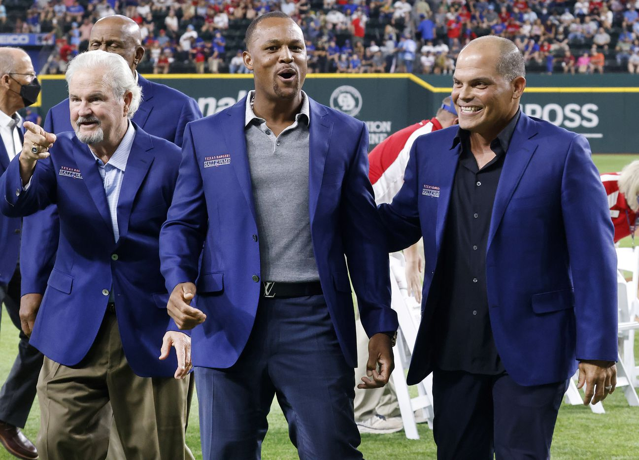 Former Texas Rangers third baseman Adrian Beltre (center) is congratulated by former Rangers catcher Ivan 'Pudge' Rodriguez (eight) after being inducted into the Texas Rangers Baseball Hall of Fame at Globe Life Field in Arlington, Saturday, August 14, 2021. Former Rangers catcher Jim Sundberg is pictured left. Executive vice president and public address announcer Chuck Morgan was also inducted. (Tom Fox/The Dallas Morning News)
