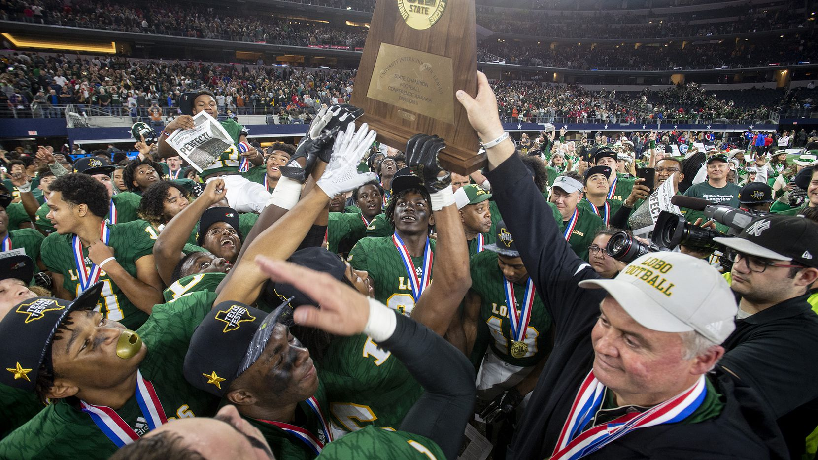 Longview won the 2018 Class 6A Division II state championship, it's first title since 1937. Head coach John King, right, helps his players hoist the trophy. (Michael Cavazos/Longview News-Journal)  The Longview Lobos celebrate their victory over Beaumont West Brook to win the Calss 6A Division II state championship game, on Saturday December 22, 2018, at AT&T Stadium in Arlington. (Michael Cavazos/ News-Journal Photo) ORG XMIT: TXLON101