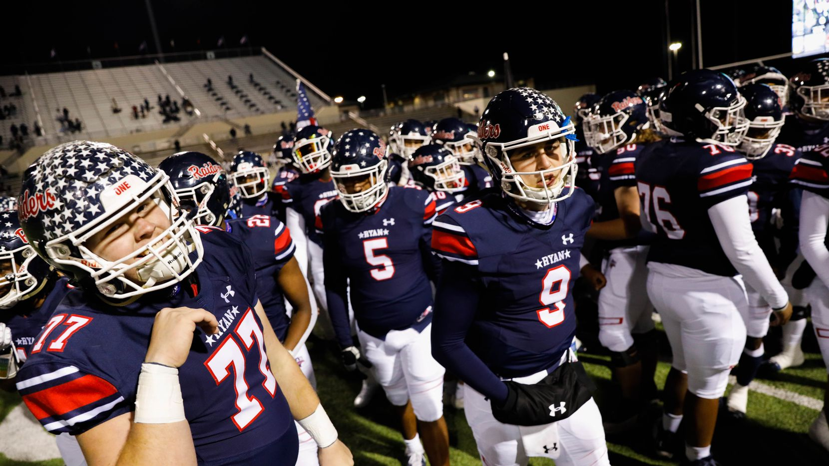 Denton Ryan's players walk to the sidelines before the start of a football game against Frisco Lone Star at the C.H. Collins Complex in Denton on Thursday, Dec. 4, 2020. The game is tied at halftime, 14-14.
