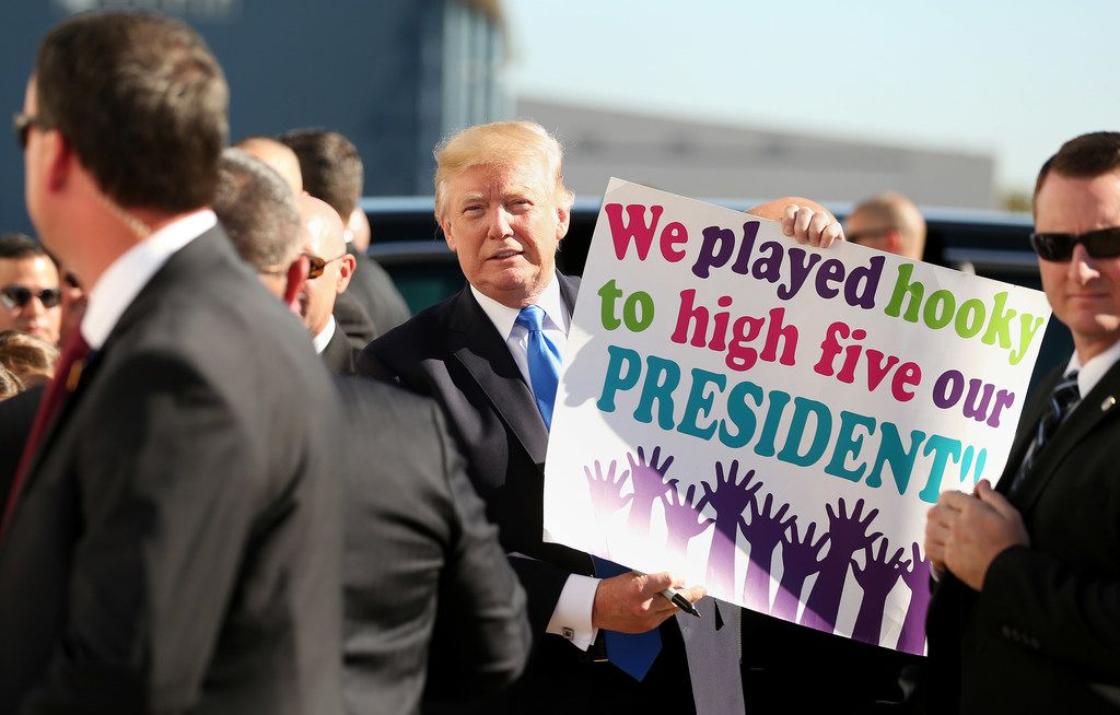 President Donald Trump holds up a supporter's sign for the media while arriving at Love Field in Dallas on October 25, 2017.