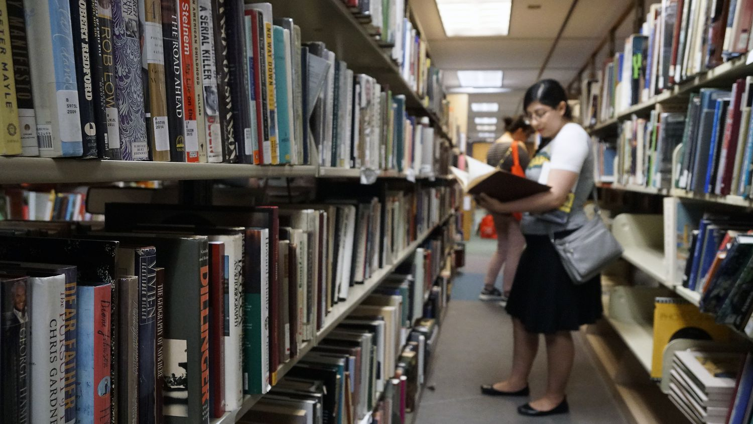 Priscilla Escobedo peruses the bookshelves during the Summer in the City discussion as part of the Dallas Festival of Books at the Dallas Public Library on Saturday, June 1, 2019.