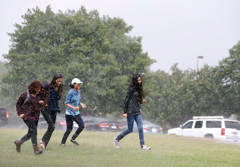 Students run towards their car as rain falls at North Lake College.