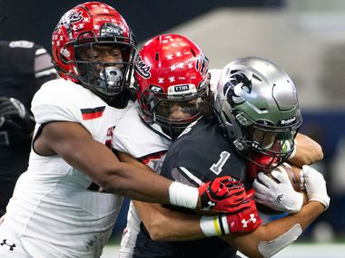 Cedar Hill defense takes down Denton Guyer running back Kaedric Cobbs (1) during the Class 6A Division II area-round high school football playoff game at the AT&T Stadium in Arlington, Texas, on Saturday, November 23, 2019.