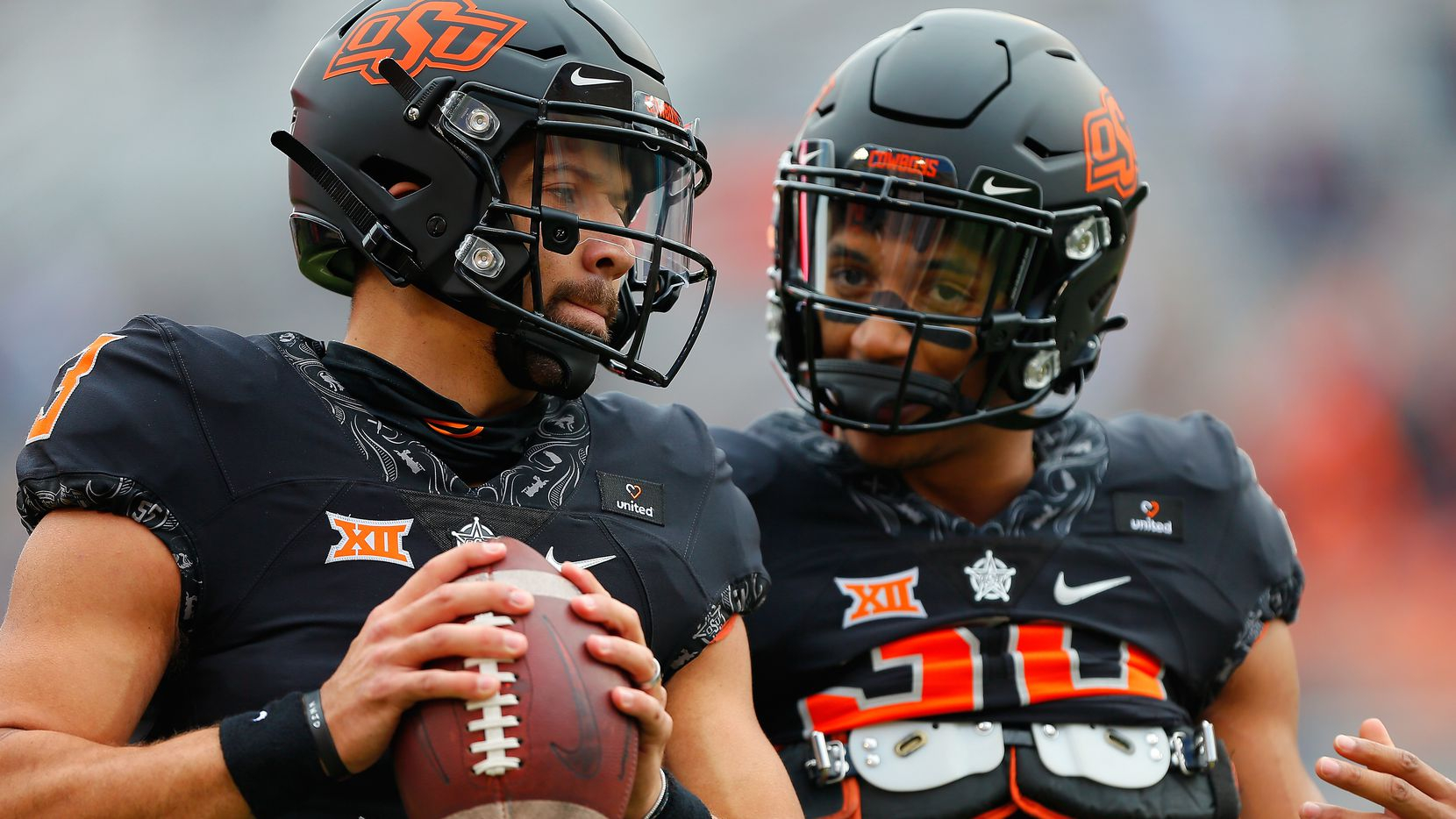 Quarterback Spencer Sanders #3 and running back Chuba Hubbard #30 of the Oklahoma State Cowboys talk before a game against the Texas Longhorns at Boone Pickens Stadium on October 31, 2020 in Stillwater, Oklahoma. (Pool Photo by Brian Bahr/Getty Images)