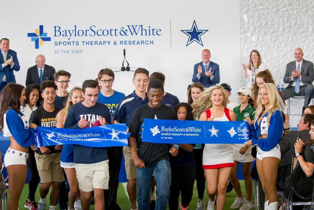 Frisco ISD students bust through a ribbon marking the official opening of Baylor Scott & White Sports Therapy & Research at The Star in Frisco on Wednesday.