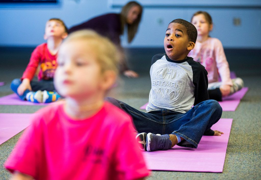 Elijah Curley (center) takes a deep breath while he and his kindergarten classmates practice yoga at Pink Elementary School.