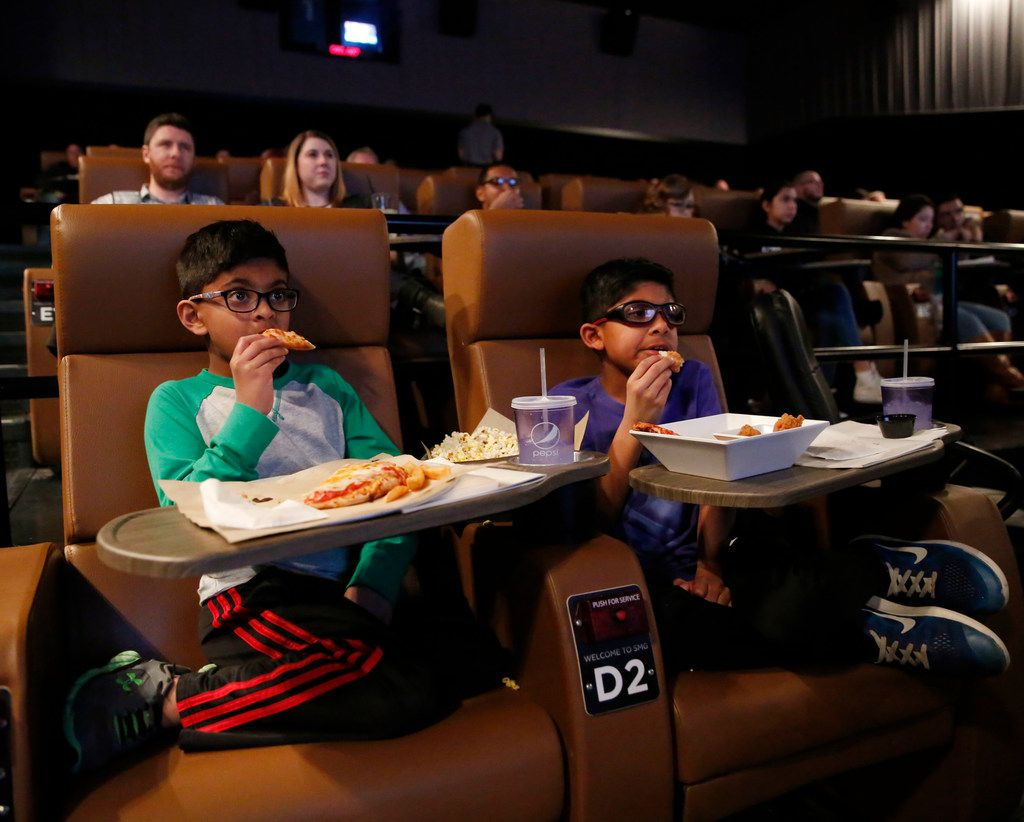 Akash Moparty, 6 and brother Jay Moparty, 9, of Lewisville watch the screen as they eat at The Studio Movie Grill in The Colony.